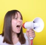 Retrato de la mujer joven que grita con un megáfono contra amarillo Imágenes de archivo libres de regalías