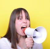Retrato de la mujer joven que grita con un megáfono contra amarillo Imagen de archivo