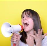 Retrato de la mujer joven que grita con un megáfono contra amarillo Foto de archivo libre de regalías
