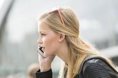 Retrato de la mujer joven que habla en el teléfono móvil Fotos de archivo libres de regalías