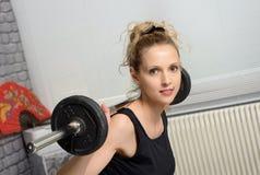Retrato de la mujer joven que hace el ejercicio con pesas de gimnasia, a de la aptitud Fotos de archivo