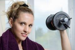 Retrato de la mujer joven que hace el ejercicio con pesas de gimnasia, a de la aptitud Fotos de archivo libres de regalías