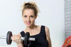 Retrato de la mujer joven que hace el ejercicio con pesas de gimnasia, a de la aptitud Imagen de archivo libre de regalías