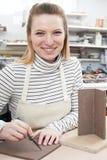 Retrato de la mujer joven que hace el pote en estudio de la cerámica imágenes de archivo libres de regalías