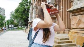 Retrato de la mujer joven que hace las fotos del edificio viejo con la cámara de la película del vintage Imagen de archivo libre de regalías
