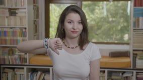 Retrato de la mujer joven que hace la negativa de los pulgares abajo y el concepto de la reacción de la aversión - almacen de metraje de vídeo
