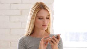 Retrato de la mujer joven que hojea Smartphone en oficina Fotos de archivo