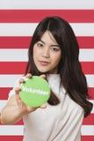 Retrato de la mujer joven que lleva a cabo hacia fuera la insignia voluntaria contra bandera americana imagen de archivo libre de regalías
