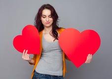 Retrato de la mujer joven que lleva a cabo un corazón de papel contra un CCB gris Imagenes de archivo