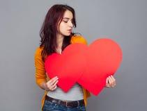 Retrato de la mujer joven que lleva a cabo un corazón de papel contra un CCB gris Foto de archivo