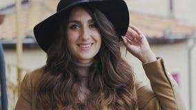 Retrato de la mujer joven que lleva en sonrisas y miradas del sombrero negro en la c?mara almacen de video