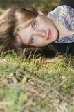 Retrato de la mujer joven que miente en la hierba Imagenes de archivo