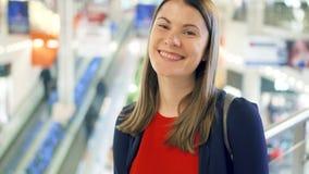 Retrato de la mujer joven que mira la cámara y la sonrisa Hembra en las compras de la alameda Concepto del consumerismo almacen de metraje de vídeo