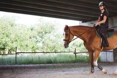 Retrato de la mujer joven que monta su caballo Fotos de archivo libres de regalías