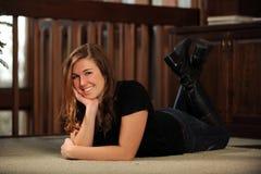 Retrato de la mujer joven que pone en suelo Imagenes de archivo