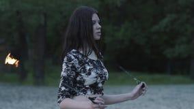Retrato de la mujer joven que realiza una demostración con la llama que se coloca en la arena Artista experto del fireshow que mu almacen de metraje de vídeo