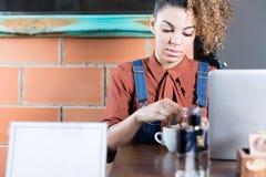 Retrato de la mujer joven que revuelve el café fotografía de archivo libre de regalías