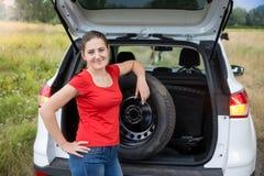 Retrato de la mujer joven que saca a coche la rueda de repuesto de tronco abierto Imagenes de archivo