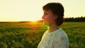 Retrato de la mujer joven que se coloca en césped verde en fondo de la puesta del sol almacen de video