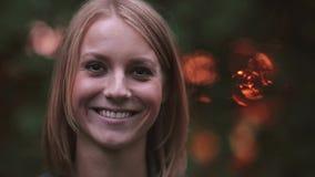 Retrato de la mujer joven que se coloca en el parque en los rayos del sol poniente, mirando a la cámara y sonriendo, primer almacen de metraje de vídeo