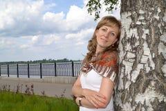 Retrato de la mujer joven que se ha inclinado contra un abedul Fotografía de archivo libre de regalías