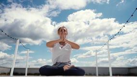 Retrato de la mujer joven que se sienta en actitud del loto y que pone las manos en namaste almacen de video