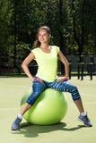 Retrato de la mujer joven que se sienta en bola del ajuste Aspecto deportivo Ejercicio en el aire abierto Imagen de archivo libre de regalías