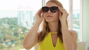 Retrato de la mujer joven que se sienta en el balcón que pone las gafas de sol Paisaje del parque y de la ciudad detrás