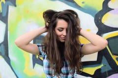Retrato de la mujer joven que se sienta en la pared de la pintada Foto de archivo libre de regalías