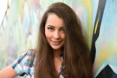 Retrato de la mujer joven que se sienta en la pared de la pintada Fotos de archivo libres de regalías