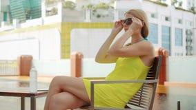 Retrato de la mujer joven que se sienta en silla cerca de la piscina que pone las gafas de sol Paisaje de la ciudad