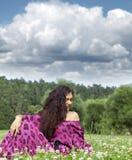 Retrato de la mujer joven que se sienta en un césped verde Fotos de archivo libres de regalías
