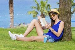 Retrato de la mujer joven que se sienta en una hierba verde con el libro en la mano Foto de archivo libre de regalías