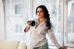 Retrato de la mujer joven que sostiene una taza de café Fotografía de archivo libre de regalías
