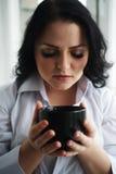 Retrato de la mujer joven que sostiene una taza de café Fotos de archivo