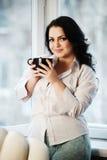 Retrato de la mujer joven que sostiene una taza de café Fotos de archivo libres de regalías