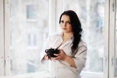 Retrato de la mujer joven que sostiene una taza de café Imagen de archivo