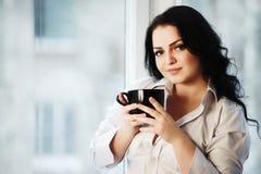 Retrato de la mujer joven que sostiene una taza de café Fotografía de archivo