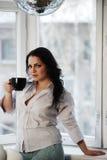 Retrato de la mujer joven que sostiene una taza de café Imagenes de archivo