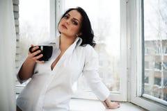 Retrato de la mujer joven que sostiene una taza de café Foto de archivo