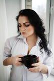 Retrato de la mujer joven que sostiene una taza de café Foto de archivo libre de regalías