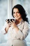 Retrato de la mujer joven que sostiene una taza de café Imagen de archivo libre de regalías