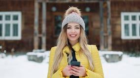 Retrato de la mujer joven que usa el app en smartphone, sonriendo y mandando un SMS en el teléfono móvil Mujer que lleva un abrig almacen de video