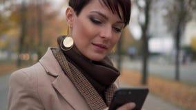 Retrato de la mujer joven que usa el teléfono en la calle almacen de metraje de vídeo