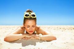 Retrato de la mujer joven relajada en la ropa de playa que pone en la costa fotos de archivo libres de regalías