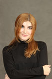 Retrato de la mujer joven roja agradable en un fondo gris Fotos de archivo