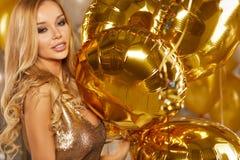 Retrato de la mujer joven rubia entre los globos y la cinta de oro Imagen de archivo