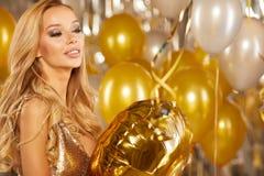 Retrato de la mujer joven rubia entre los globos y la cinta de oro Foto de archivo libre de regalías