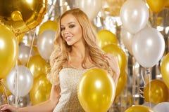 Retrato de la mujer joven rubia entre los globos y la cinta de oro Imágenes de archivo libres de regalías