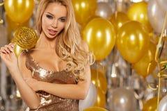 Retrato de la mujer joven rubia entre los globos y la cinta de oro Foto de archivo
